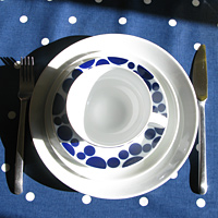 White plates with a white bowl on top, set upon a blue tablecloth with white spots, with a knife on the right side and a fork on the left side